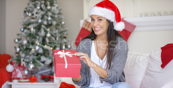 Stock photo: Excited young woman opening a Christmas gift