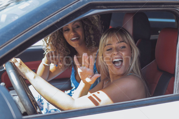 Coquettish girls in car flirting with pedestrian Stock photo © dash