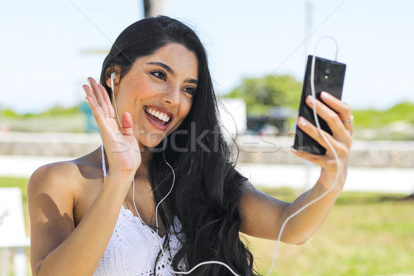 Laughing girl chatting online with phone in park Stock photo © dash