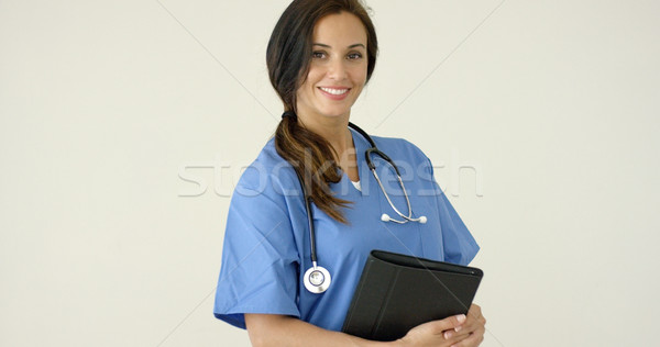 Woman in scrubs holds black portfolio and smiles Stock photo © dash