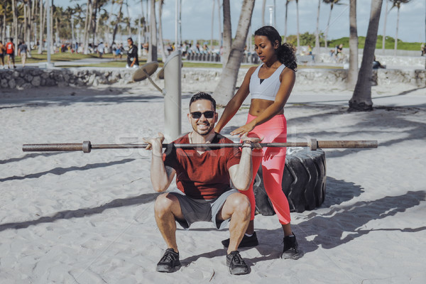 Woman helping man with workout on beach Stock photo © dash