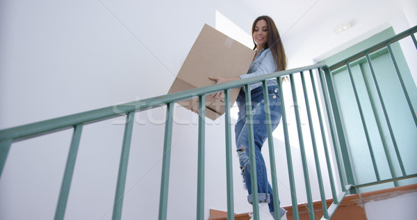 Young woman carrying a carton downstairs Stock photo © dash
