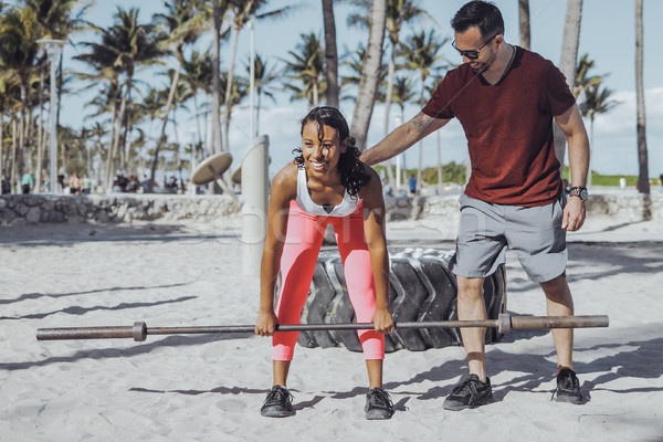 Man supporting girl with squats on beach Stock photo © dash