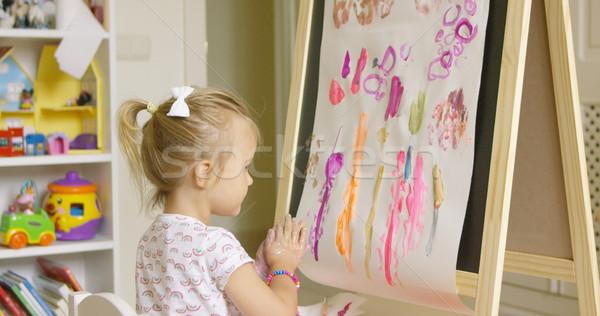 Artistic little girl painting a creative design Stock photo © dash