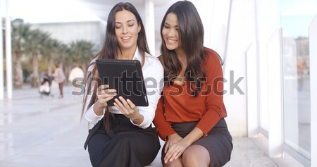 Two pretty stylish women reading an sms Stock photo © dash