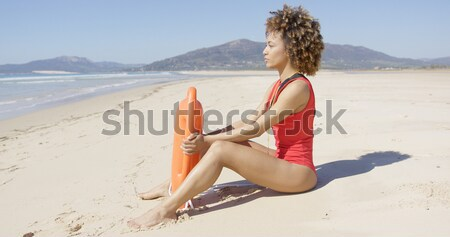 Female with rescue float sitting on beach Stock photo © dash