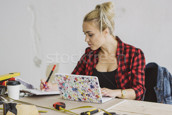 Female with laptop writing in notebook  Stock photo © dash