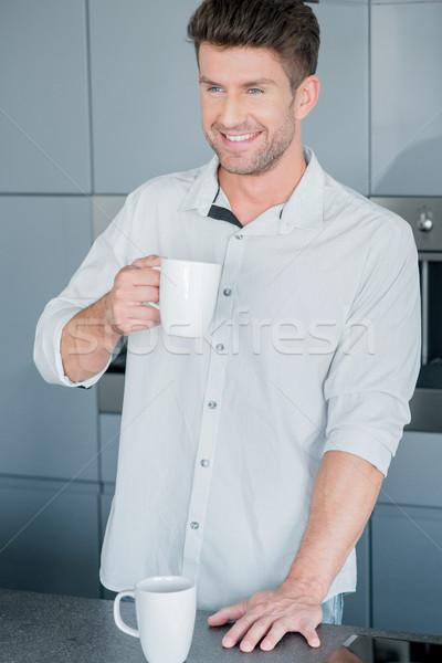 Handsome man enjoying a mug of fresh coffee Stock photo © dash