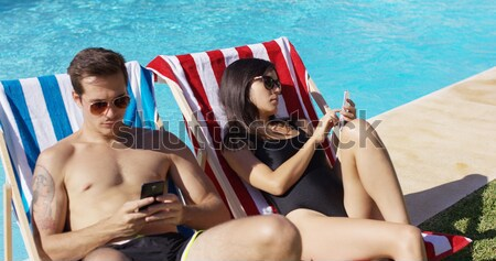 Relaxed attractive young couple reading poolside Stock photo © dash