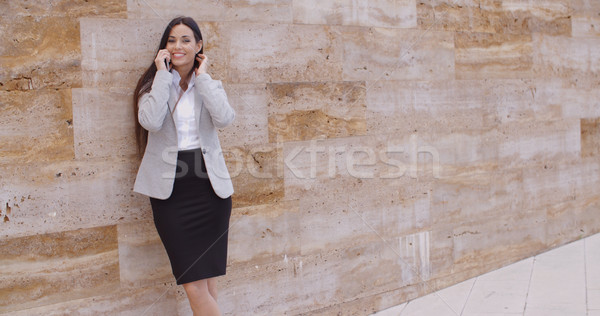 Pretty woman talking on phone and leaning on wall Stock photo © dash