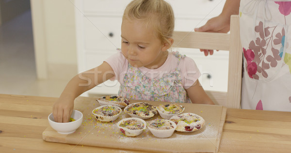 Stock photo: Close up on girl sprinkling toppings  muffins