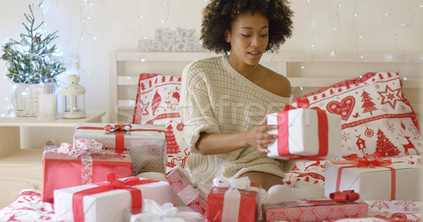 Young woman sitting in bed surrounded by gifts Stock photo © dash