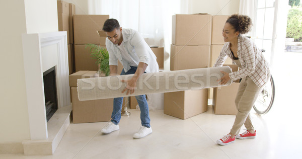 Young couple carrying a rolled rug into a house Stock photo © dash