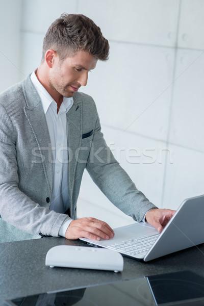 Stylish man sitting typing on a laptop Stock photo © dash