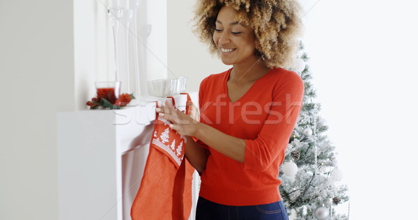 Happy young woman hanging Christmas stockings Stock photo © dash