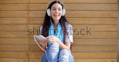 Mulher jovem ouvir música móvel telefone móvel estéreo Foto stock © dash