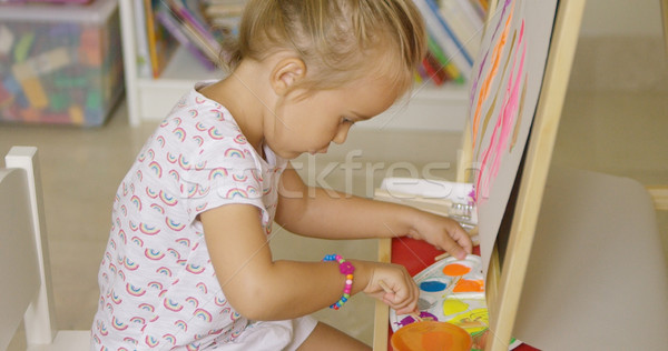 Cute little girl mixing paints for her painting Stock photo © dash