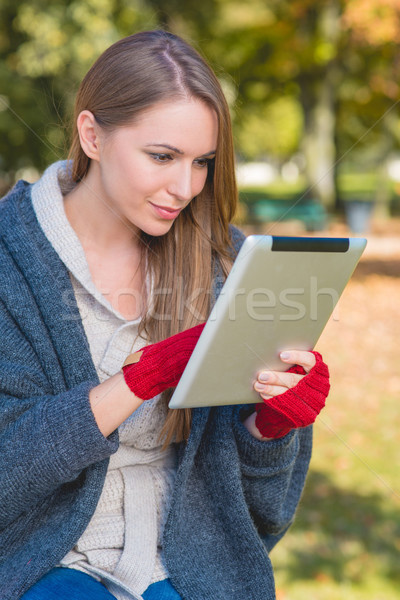 Smiling Young Woman Busy with Apple Ipad Stock photo © dash