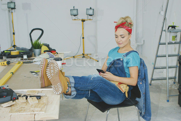 Woman resting with smartphone at carpenter workbench  Stock photo © dash