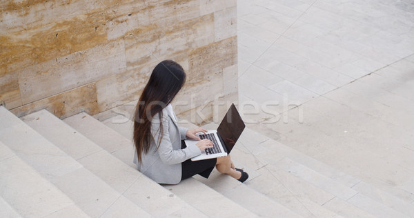 Stock photo: High angle view of woman on laptop on stairs
