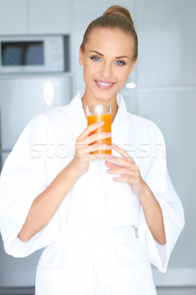 Woman in bath robe drinking orange juice Stock photo © dash