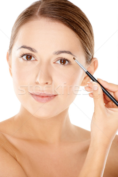 Stock photo: Woman holding a tiny cosmetic brush