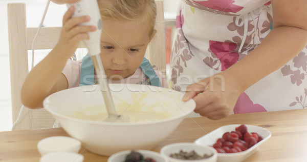 Serious pretty little girl concentrating on baking Stock photo © dash