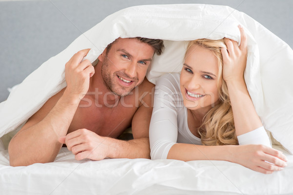 Young couple covering themselves in the duvet Stock photo © dash