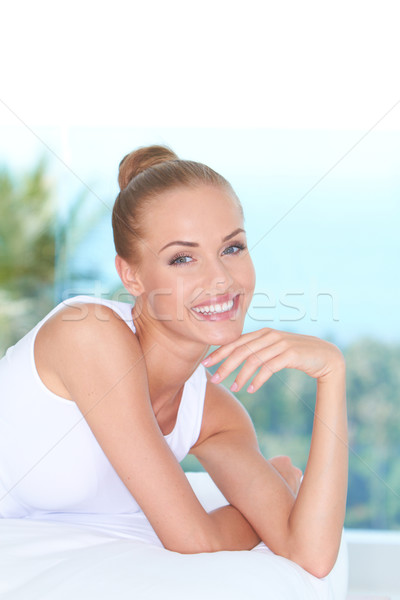 Attractive Smiling Woman Lying Prone on Bed Stock photo © dash