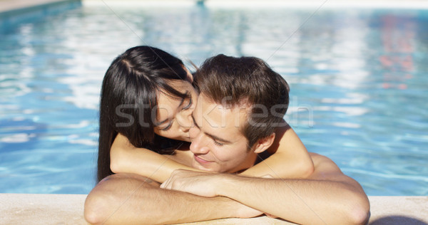 Beautiful woman cuddles with her boyfriend in pool Stock photo © dash