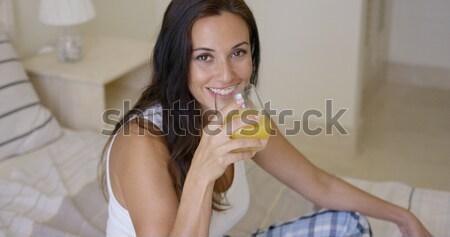 Vivacious woman enjoying a glass of fresh orange Stock photo © dash