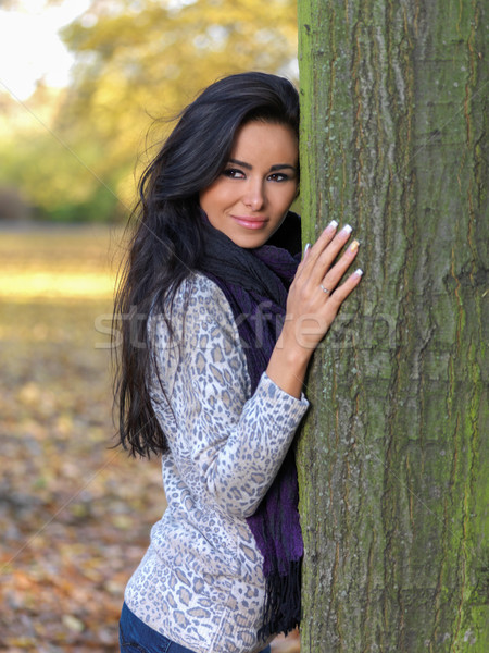 Smiling Pretty Young Woman Leaning on Tree Trunk Stock photo © dash