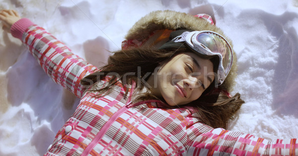 Young woman lying on snow with ski goggles Stock photo © dash