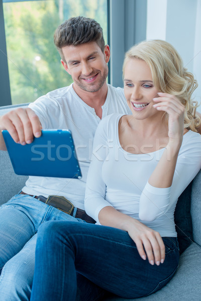 Couple smiling and laughing as they read a tablet Stock photo © dash