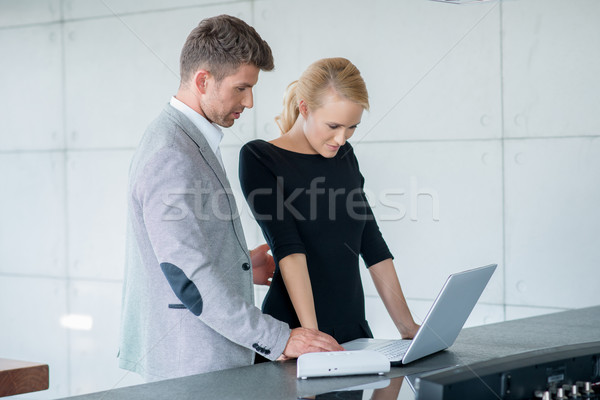 Professional Couple Looking Down at Laptop Stock photo © dash