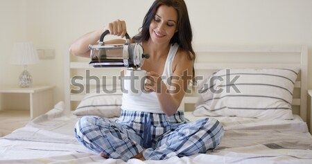 Laughing playful young woman relaxing in bed Stock photo © dash