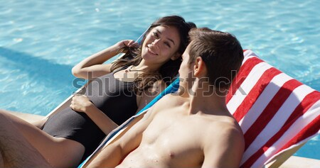 Three sexy young girlfriends relaxing poolside Stock photo © dash