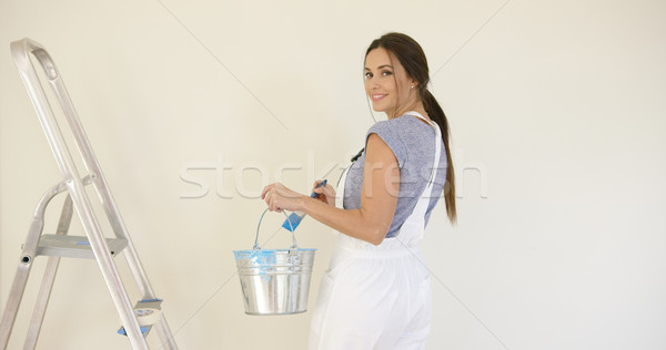 Stock photo: Smiling attractive woman painting her home