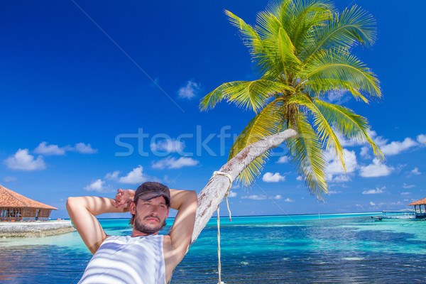Gorgeous Man Resting on Beach Palm Tree Stock photo © dash