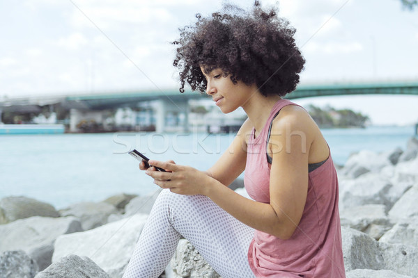 Casual young woman using phone on embankment Stock photo © dash