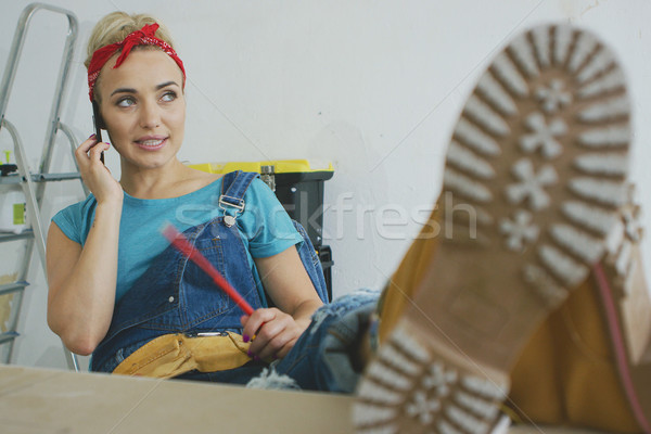 Woman carpenter at workbench talking on smartphone Stock photo © dash