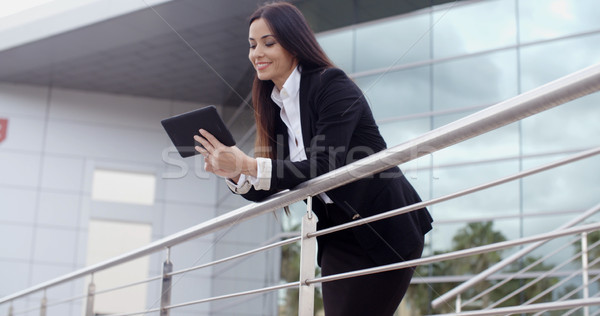 Young businesswoman browsing on her tablet Stock photo © dash