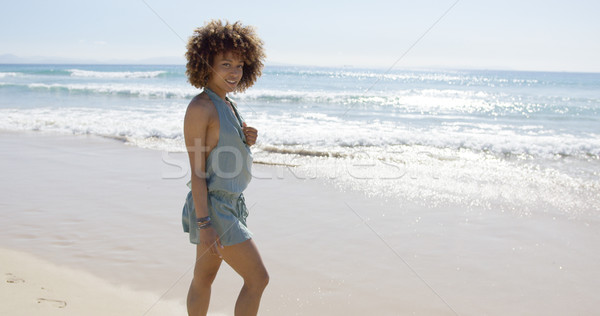 Female wearing jumpsuit walking along beach Stock photo © dash