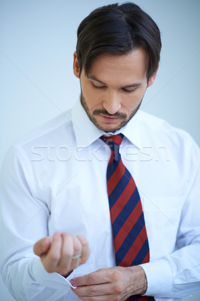 Attractive young man doing up his shirt cuffs Stock photo © dash