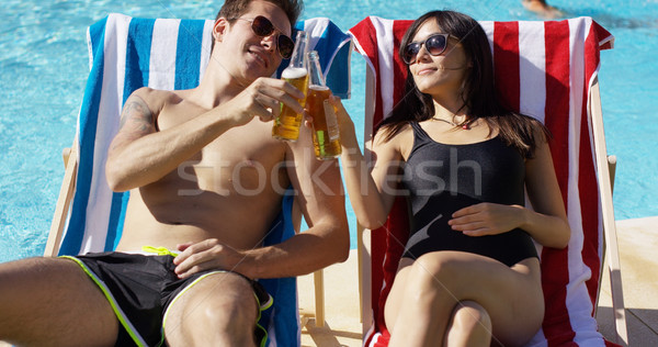 Attractive young couple enjoying a beer Stock photo © dash