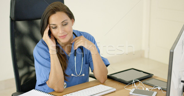 healthcare worker wearing scrubs sits at computer Stock photo © dash