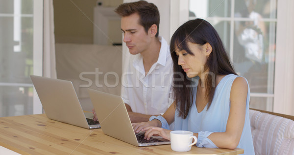 Calm young couple sitting at table using laptop Stock photo © dash
