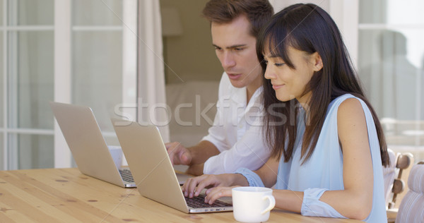 Couple working on laptop computers together Stock photo © dash