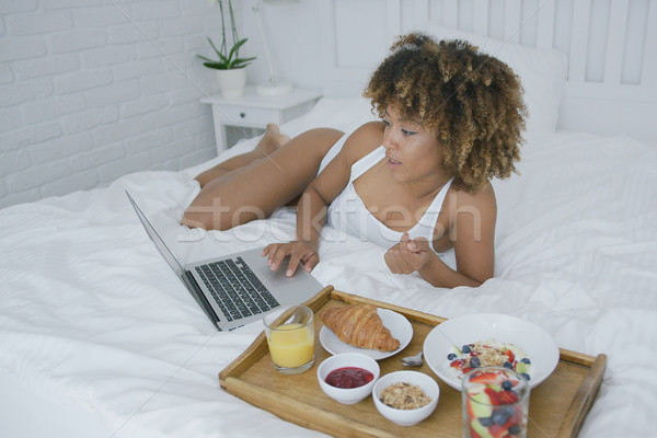 Content woman using laptop while having meal Stock photo © dash