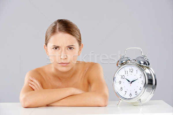 Woman with Arms Crossed Next to Alarm Clock Stock photo © dash